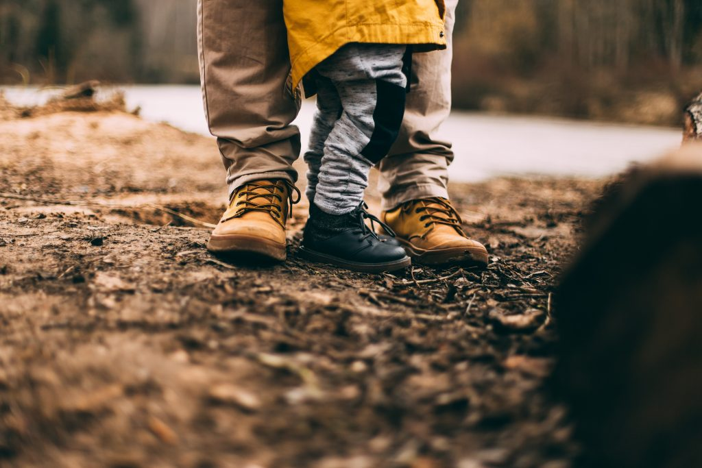 A parent stands with their child on a muddy floor