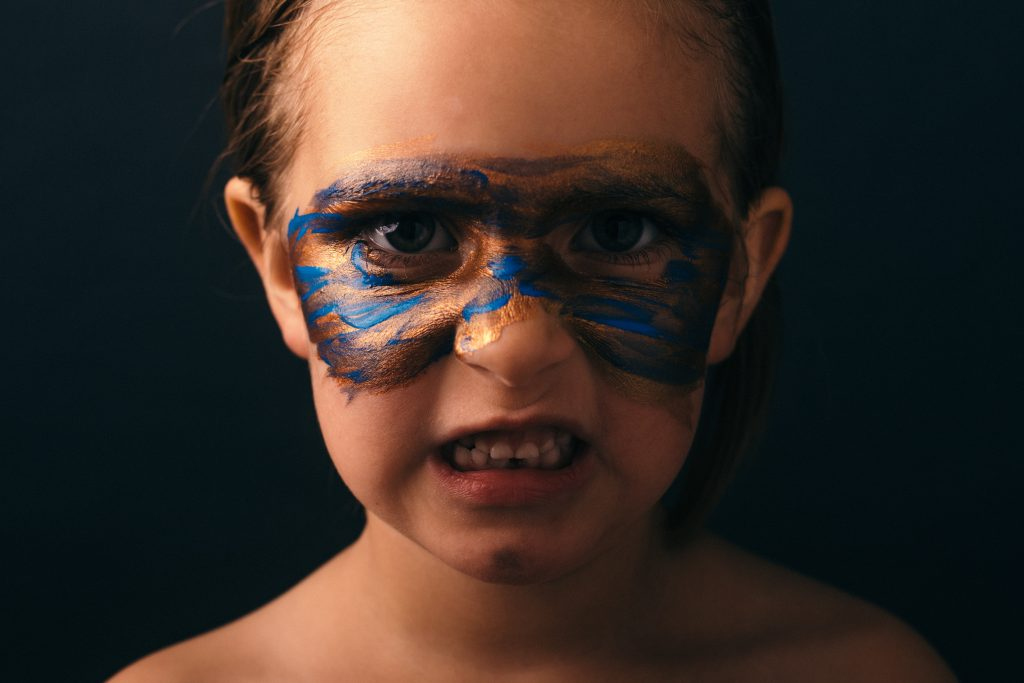 A young boy with face paint wearing an angry face
