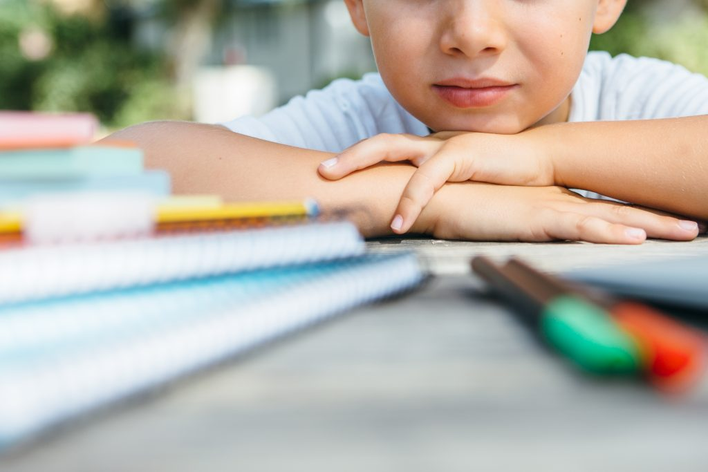Young boy lays with head on a table looking at books
