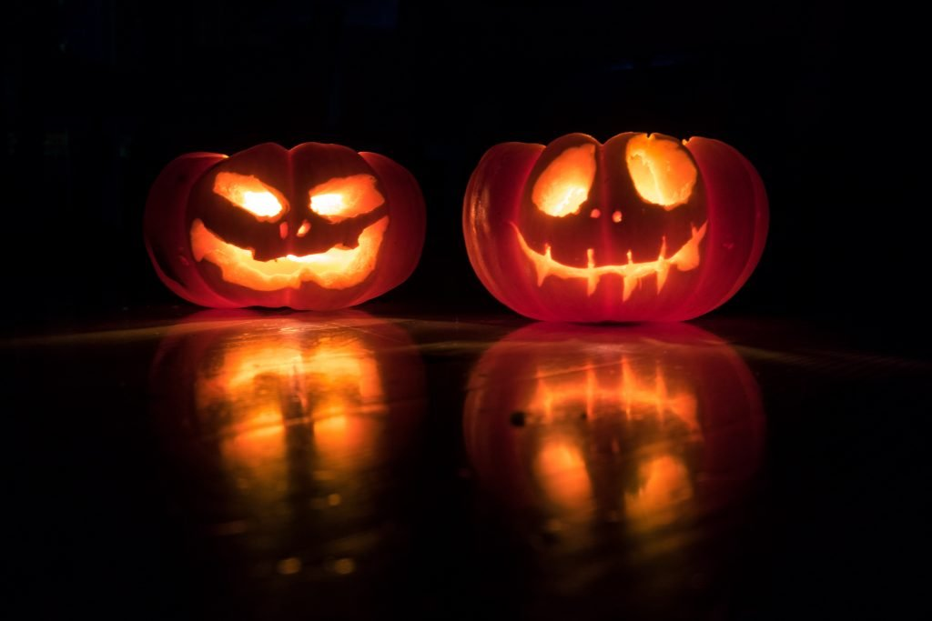 Two pumpkins with faces carved into them lit up on a dark night.