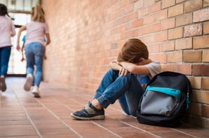 Young boy sitting downcast on the floor with his back to a wall at school.