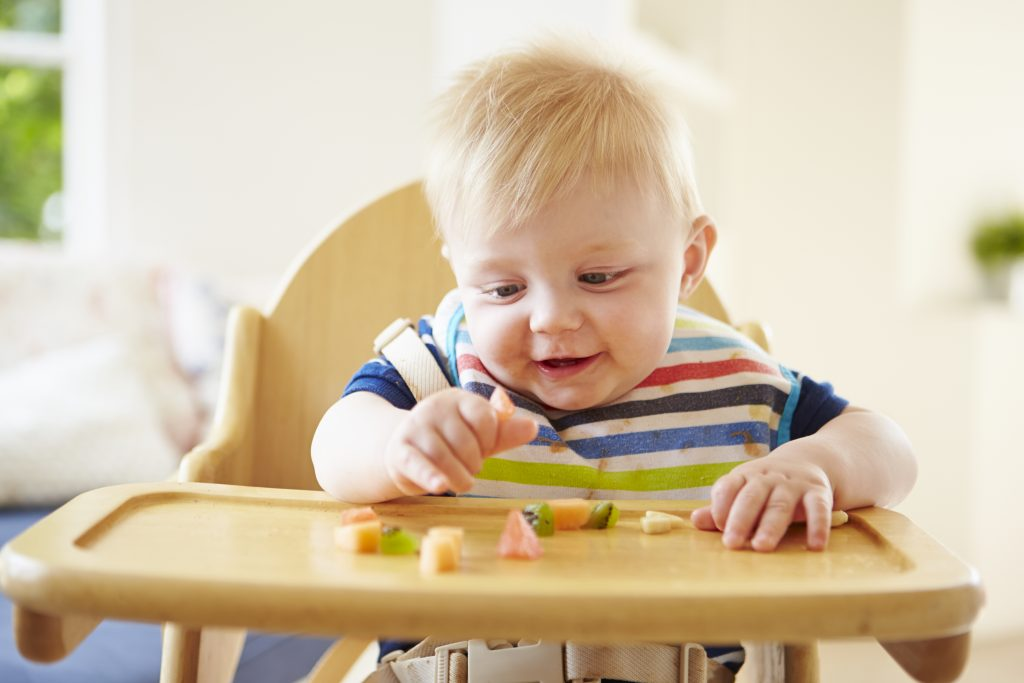 Toddler sits in a high chair playing with some fruit on his table