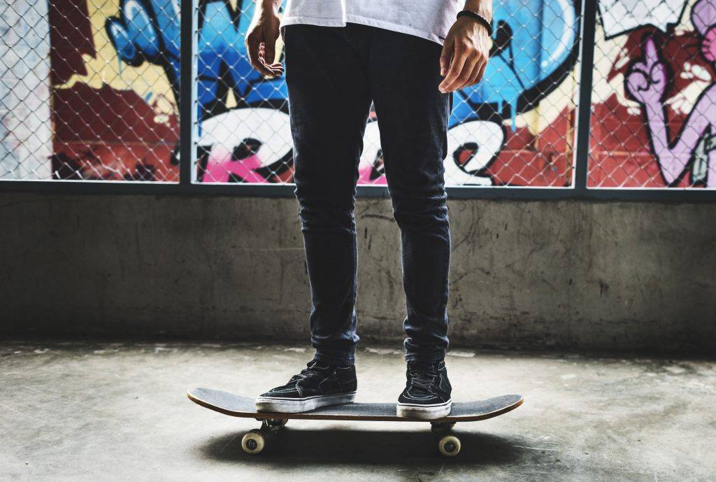 Teenaged boy stands on a skateboard in the middle of a skate park