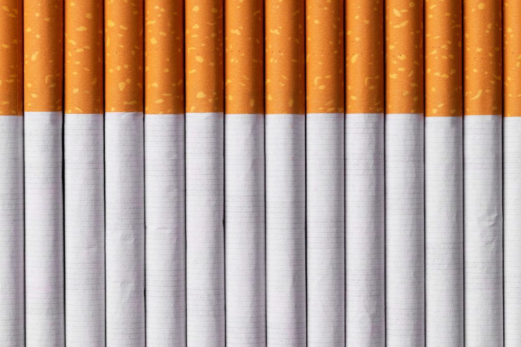 Multiple cigarettes organized in a row over purple background