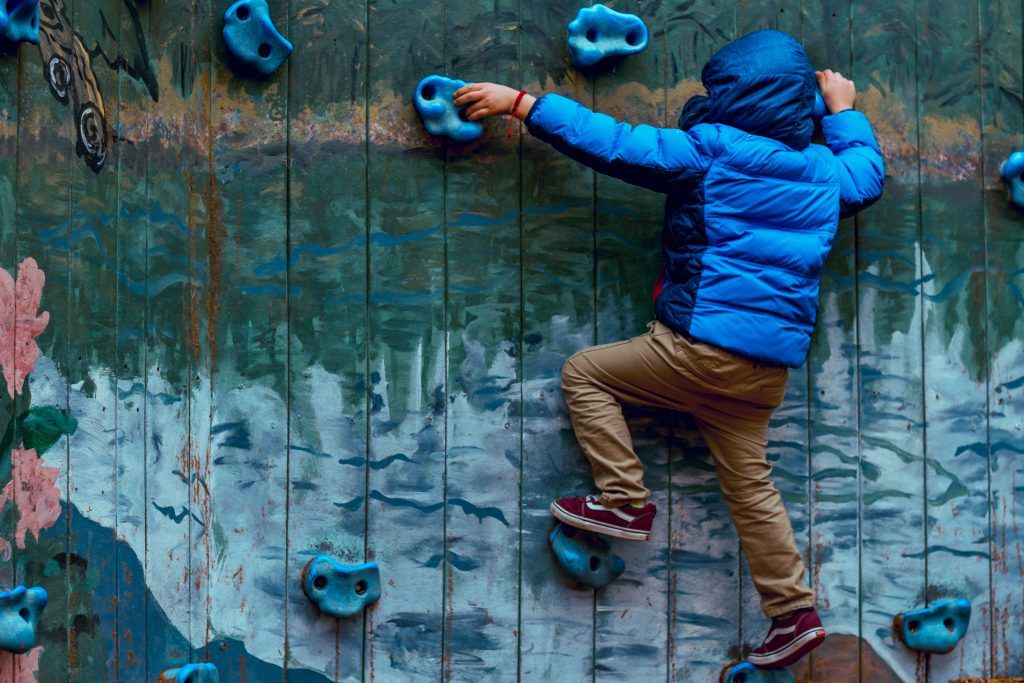 Young boy climbing a blue wall in his waterproof jacket.