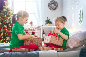 Two young girls sat on a bed opening an array of Christmas gifts.