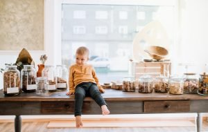 Young boy sitting and moving closer to the sweets on a desk