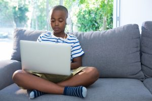 Young boy sitting on a sofa with a laptop and headphones.