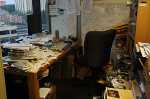 An office filled with an assorment of papers, CDs and mess.