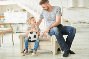 Dad in a grey shirt helping his son who is sitting with a football