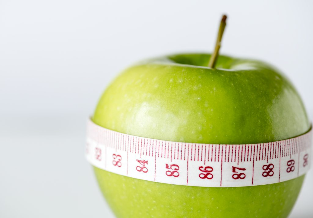 An apple with a measureing tape around it.