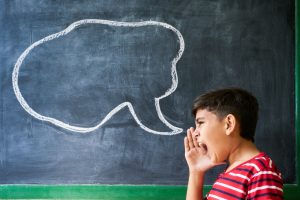 Young boy yelling into a speech bubble that is drawn onto a blackboard in a classroom.