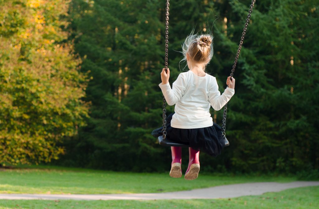 Little girl on a swing looks into the distance.