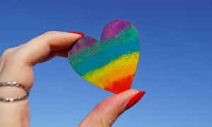 Person holding a heart shaped pride flag