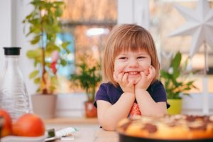 Young child sitting at a table looking cheeky