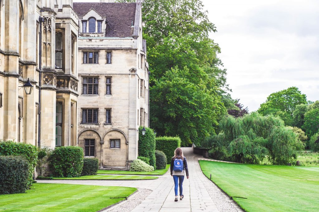 Girl walking past a Kings college building.