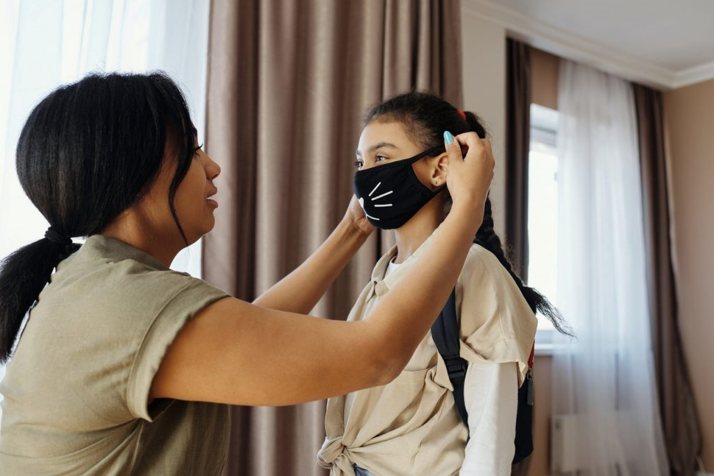 Young girl having a face mask placed by female caretaker