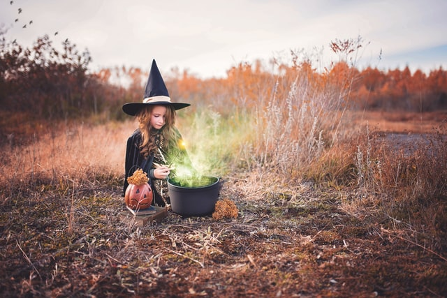 Young girl sitting in field making a potion
