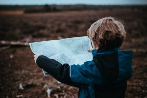 Young boy looks over a map on his way to an adventure building resilience.