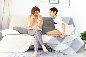Boy yelling at mother who sits on a sofa.