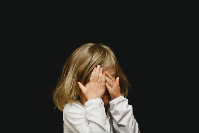 Young girl on a dark background with hands oover her face