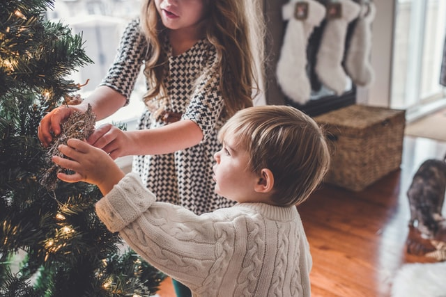 Girl in a dress helps her sibling place ornament on a christmas tree