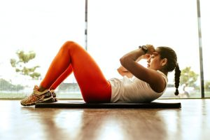 Woman doing crunches on a mat in a workout room