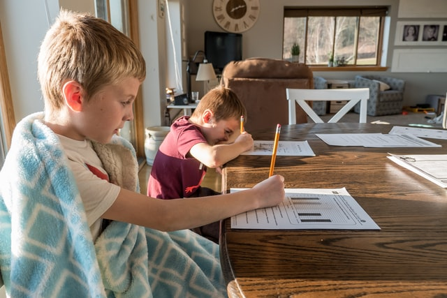 Two boys writing for school work