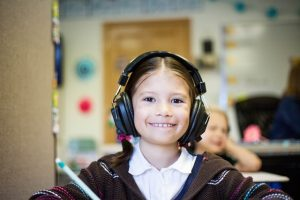 Young girl in a classroom smiling with headphones