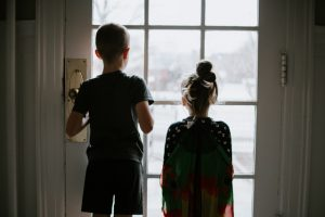 A pair of siblings standing at the door to their house
