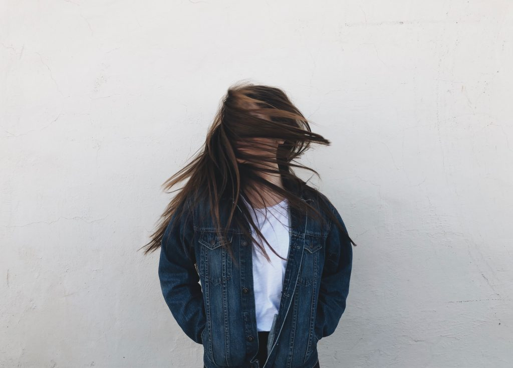 Girl in a hallway hiding her face with her hair because of imposter syndrome