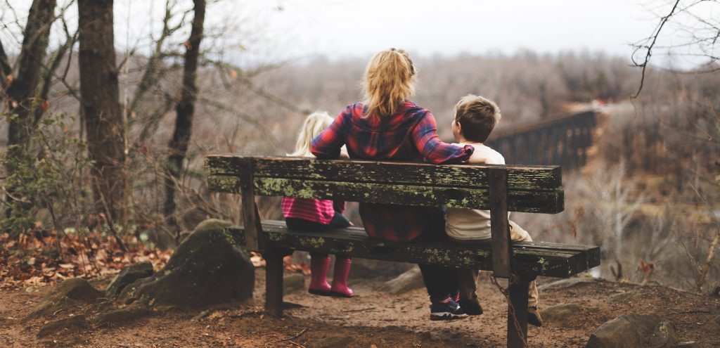 Mum sits on a bench with her children talking