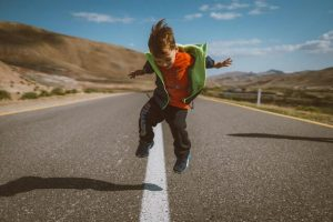 Young boy in the middle of an empty road jumping with confidence