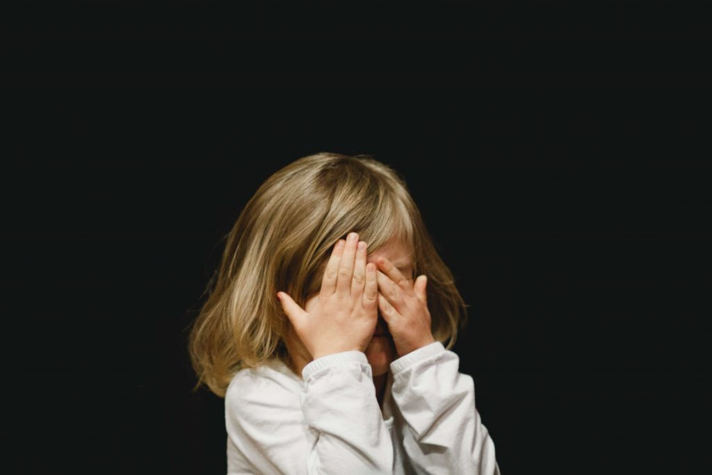 Young child hiding their face after telling a lie